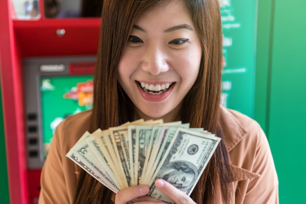 Premium Photo | Happy asian young woman holding the dollar money