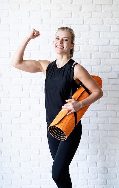 白いレンガの壁の背景に彼女の上腕二頭筋を示す黒いスポーツウェアの幸せな運動女性 Premium写真