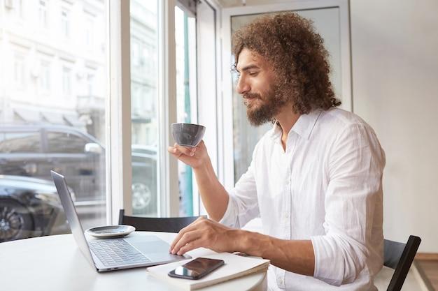 ノートパソコンで窓の隣のテーブルに座って、画面を楽しく見て、お茶を飲み、白いシャツを着て、幸せな魅力的なひげを生やした男 無料写真