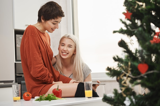 Happy attractive blonde girl holding tablet and smiling at camera while sitting next to her lovely girlfriend in kitchen near christmas tree. women laughing over article they read via gadget. Free Photo
