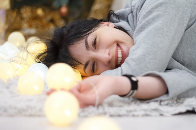 Happy attractive brunette girl lying at home with a garland of lights Premium Photo