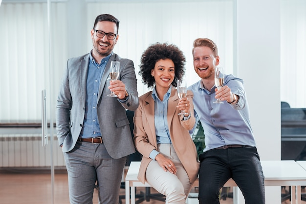 Happy attractive business people holding glass of champagne. Premium Photo
