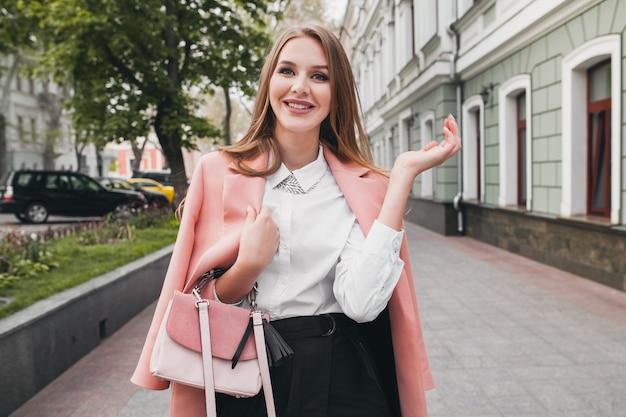 ピンクのコートで街を歩いて幸せな魅力的なスタイリッシュな笑顔の女性 無料写真
