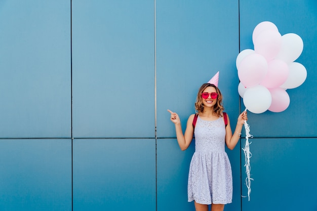 Happy attractive woman in sunglasses and party hat, holds air balloons Free Photo