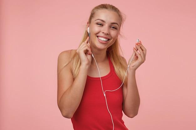 Счастливая привлекательная молодая женщина с длинными светлыми волосами, торчащими из наушников во время прослушивания музыки, в повседневной одежде, изолированные Бесплатные Фотографии