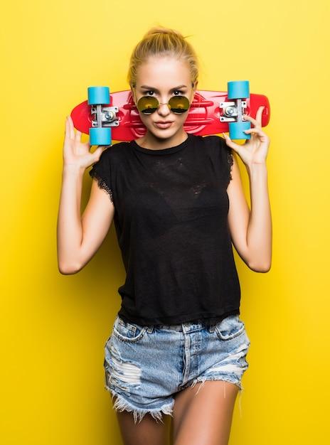 Счастливая привлекательная молодая женщина в солнцезащитных очках, сидя на скейтборде на желтом фоне Бесплатные Фотографии