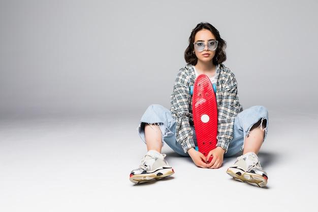 スケートボードの上に座ってサングラスで幸せな魅力的な若い女性 無料写真