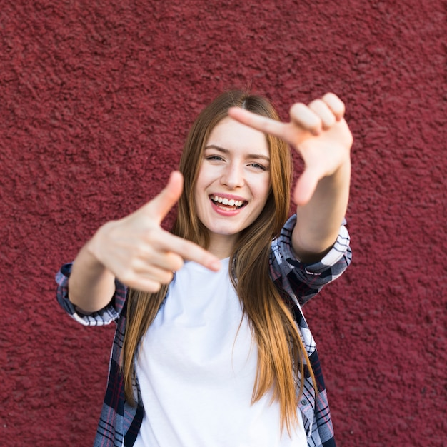 Happy attractive young woman making hand frame against red wall Free Photo