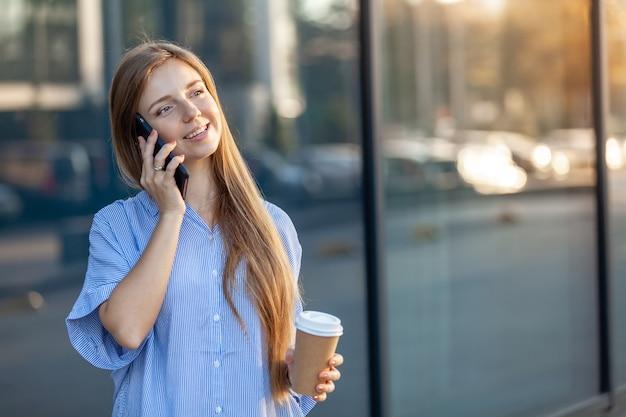 Счастливый привлекательная молодая женщина, говорить на смартфоне, держа забрать чашку кофе Premium Фотографии