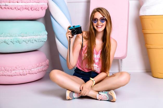Счастливая привлекательная молодая женщина с забавными солнечными очками сердец, улыбаясь и принимая фото на камеру. сногсшибательная молодая блондинка-фотограф позирует возле поддельных миндальных печений и мороженого. сидя на полу. Бесплатные Фотографии