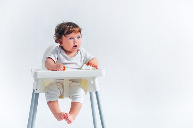 Happy baby boy sitting on baby chair Free Photo