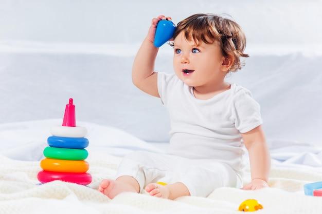 Neonato felice che si siede con il giocattolo Foto Gratuite