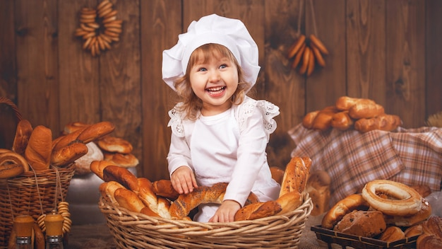 Happy baby chef in wicker basket laughing Premium Photo