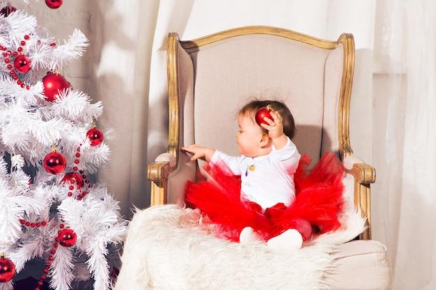 Счастливый малыш девочка возле елки Premium Фотографии