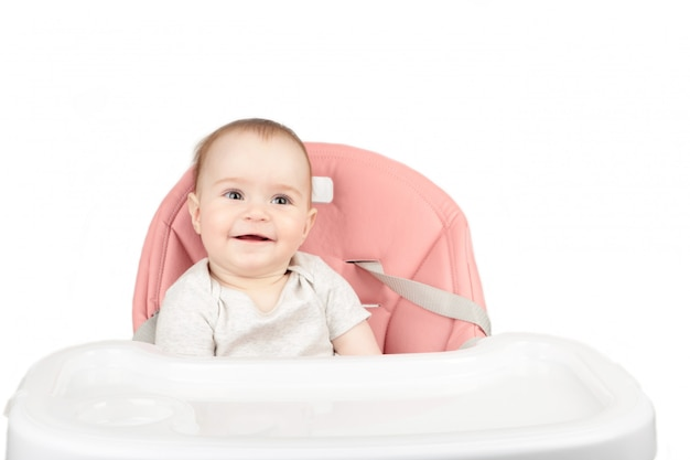 Happy baby girl sitting in a high chair and smile isolated on white background Premium Photo