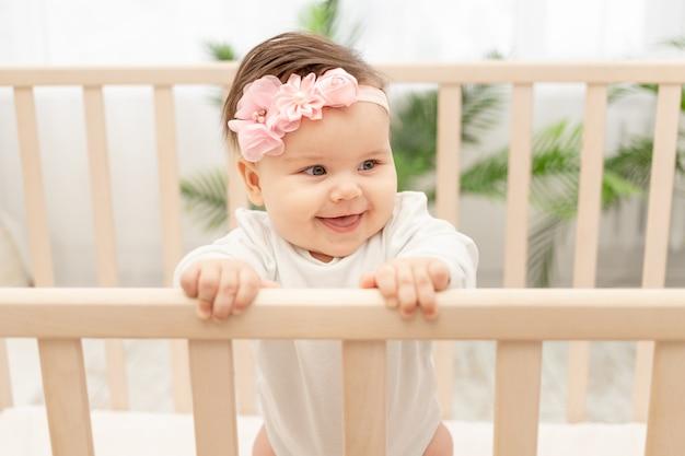 Счастливая девочка шесть месяцев стоя в кроватке Premium Фотографии