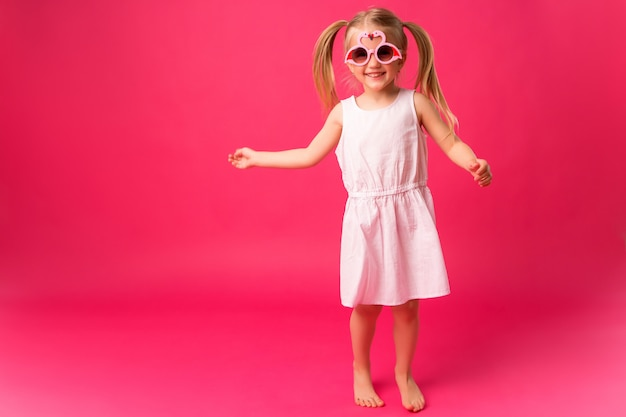 Happy baby girl smiling in sunglasses on pink background Premium Photo