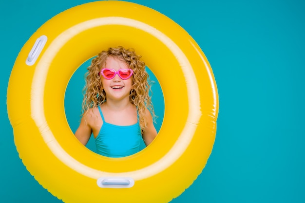 Happy baby girl in swimsuit with circle isolated on blue background Premium Photo