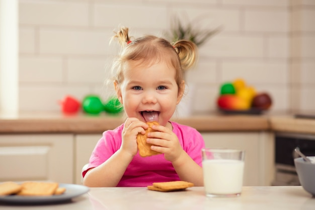 キッチンのテーブルに座って食欲をそそる幸せな赤ちゃん Premium写真