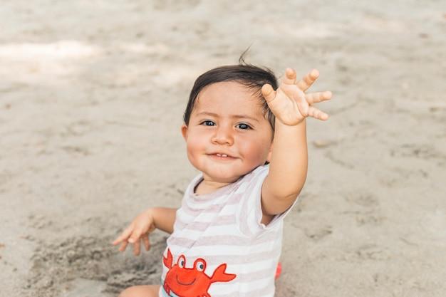 Happy baby sitting on sand Free Photo