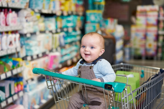 Happy baby smiling in trolley in grocery store Premium Photo