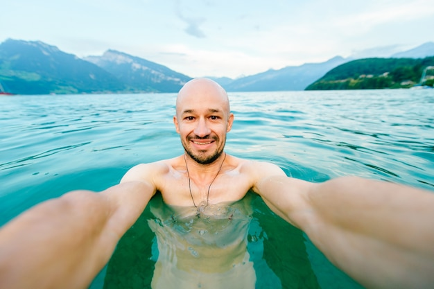 Happy bald man taking selfie in summer lake with mountains Premium Photo