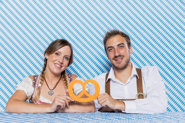 Happy bavarian couple holding a pretzel Free Photo