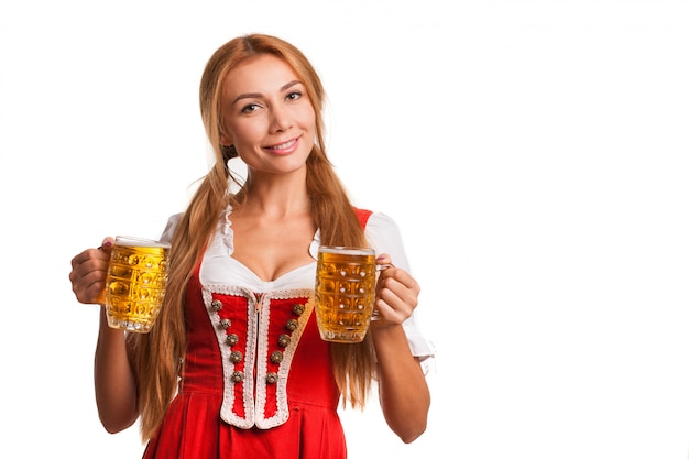 Happy bavarian girl smiling to the camera, holding mugs of beer. attractive german woman in traditional oktoberfest dress serving beers, copy space Premium Photo