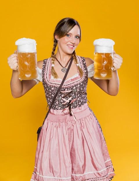 Счастливая баварская женщина, держащая пивные кружки Бесплатные Фотографии