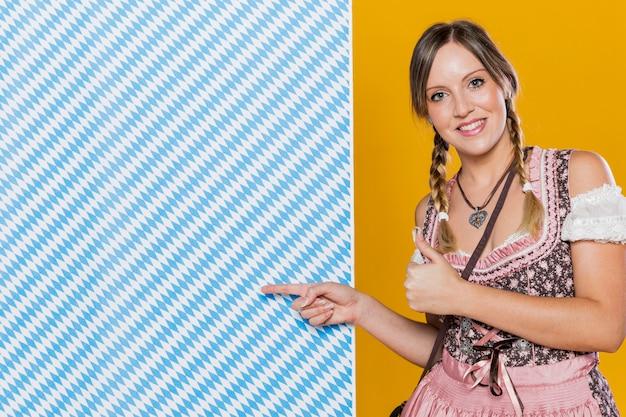 Happy bavarian woman pointing at pattern Free Photo