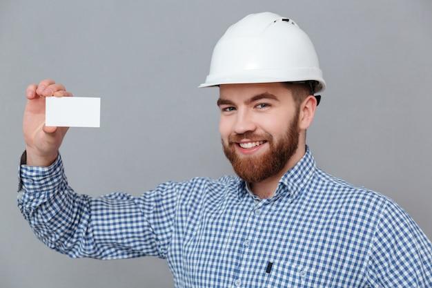 Costruttore barbuto felice che tiene biglietto da visita in bianco Foto Gratuite