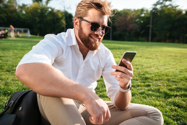 Happy bearded man in sunglasses and business clothes sitting on grass outdoors and using his smartphone Free Photo