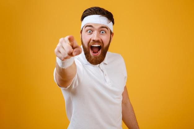 Счастливый бородатый спортсмен, указывая на камеру Бесплатные Фотографии