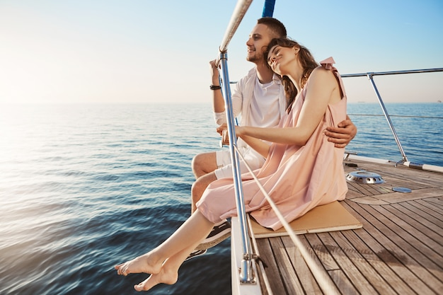 Happy beautiful adult couple sitting on side of yacht, watching at seaside and hugging while on vacation. tan might fade but such memories you share with one you love, last forever Free Photo