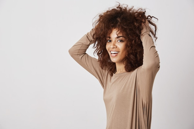 Happy beautiful african girl smiling touching her hair. white wall. Free Photo