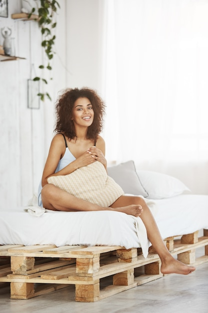 Happy beautiful african woman in sleepwear smiling holding pillow sitting on bed at home in her loft apartment. Free Photo