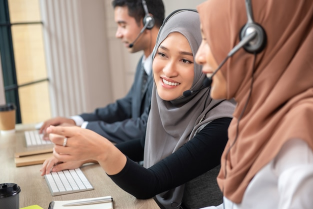 Happy beautiful asian muslim women working in call center office Premium Photo