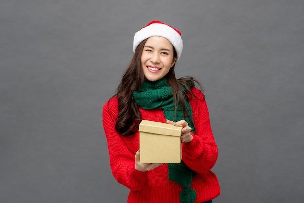 Happy beautiful asian woman in christmas attire opening gift box Premium Photo