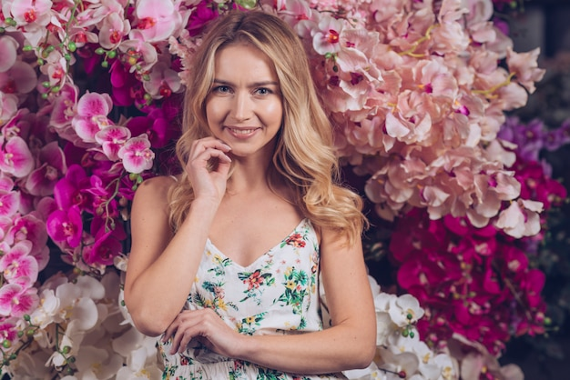 Happy beautiful blonde young woman with hand on chin standing in front of orchid flowers Free Photo