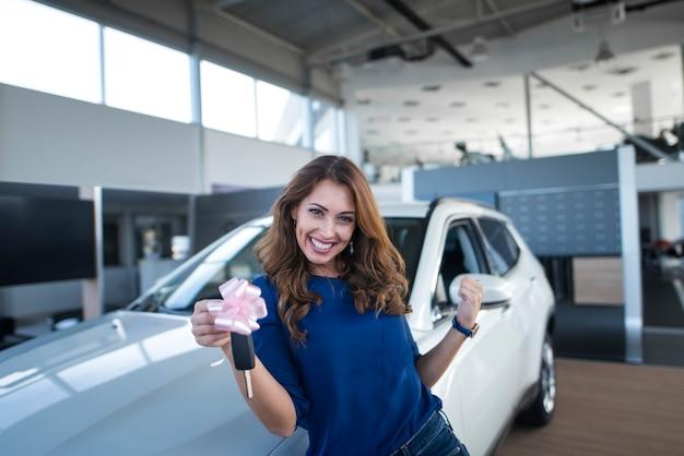 自動車販売店のショールームで新車の前に車のキーを保持している幸せな美しいブルネットの女性 無料写真
