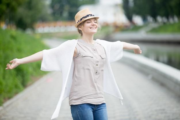 Happy beautiful caucasian woman in summer feeling joyful outdoors Free Photo