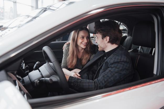 Happy beautiful couple is choosing a new car at dealership Premium Photo
