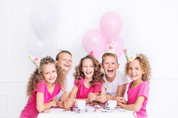 행복 한 아름 다운 귀여운 아이 화이트 룸의 테이블에 풍선과 색종이 함께 휴가 파티에서 미소 프리미엄 사진
