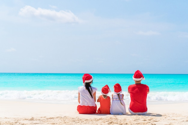 Happy beautiful family in red santa hats on a tropical beach celebrating christmas Premium Photo