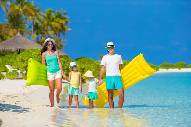 Happy beautiful family on white beach with inflatable air mattresses and toys Premium Photo