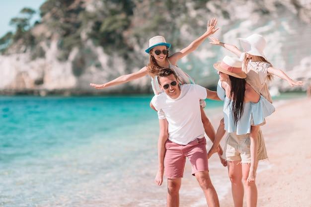 ビーチで子供たちと幸せな美しい家族 Premium写真