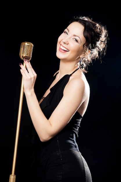 Happy beautiful girl singer laughing behind retro microphone Free Photo