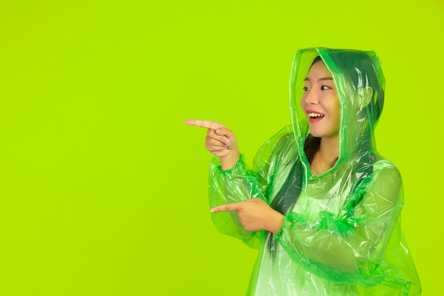 Happy beautiful girl, wearing green clothes, umbrella and coat. rainy day. Free Photo