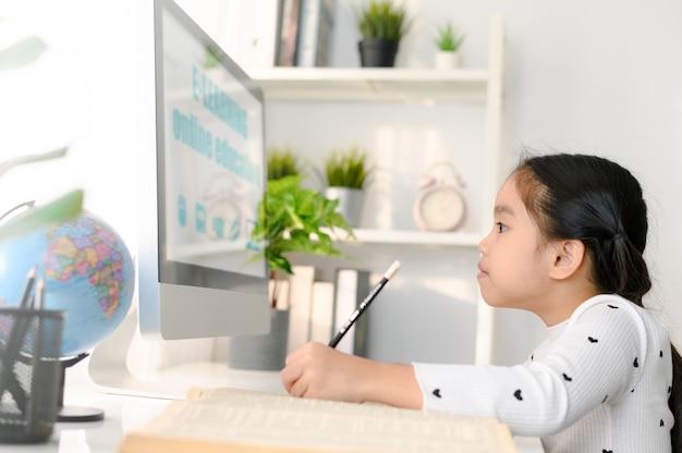 Счастливый красивый студент маленькой девочки, использующий компьютер, чтобы учиться через электронное обучение онлайн Premium Фотографии