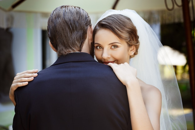 Happy beautiful newlyweds smiling, embracing in cafe outdoors. Free Photo